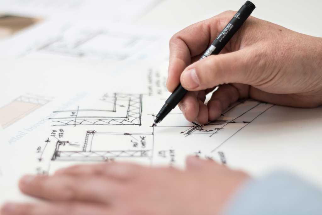 man drawing blueprint of custom home