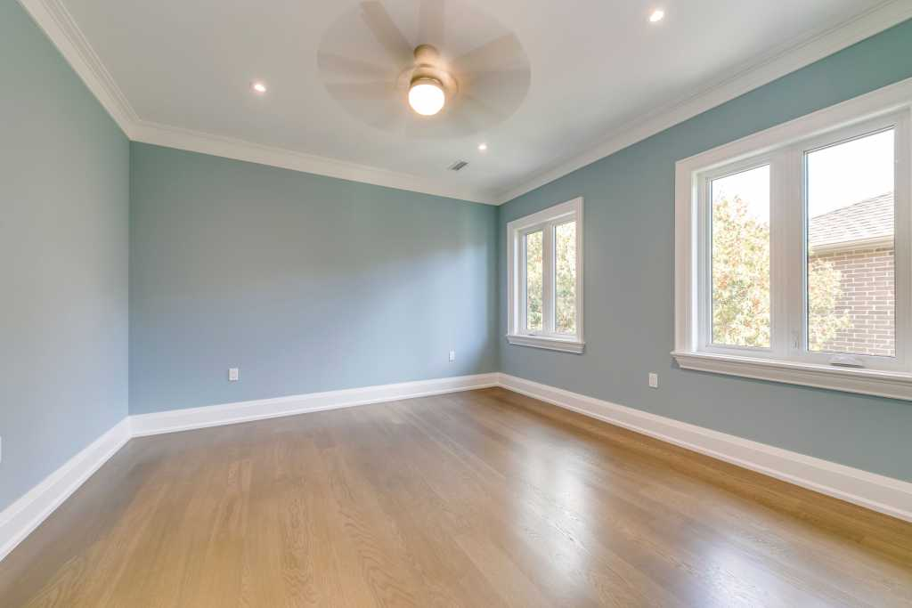 modern bedroom with blue wall painting and baseboard trim - builders in toronto