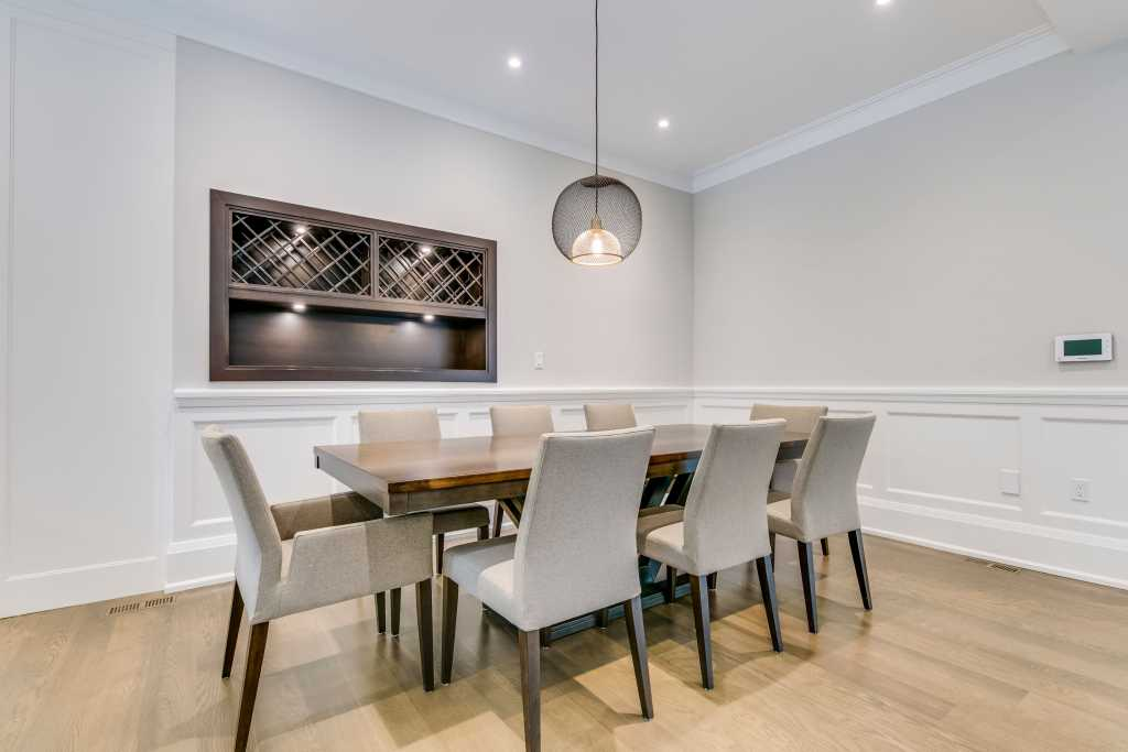 amazing dining room with build in storage space and coffered wall decor - custom home builders Toronto