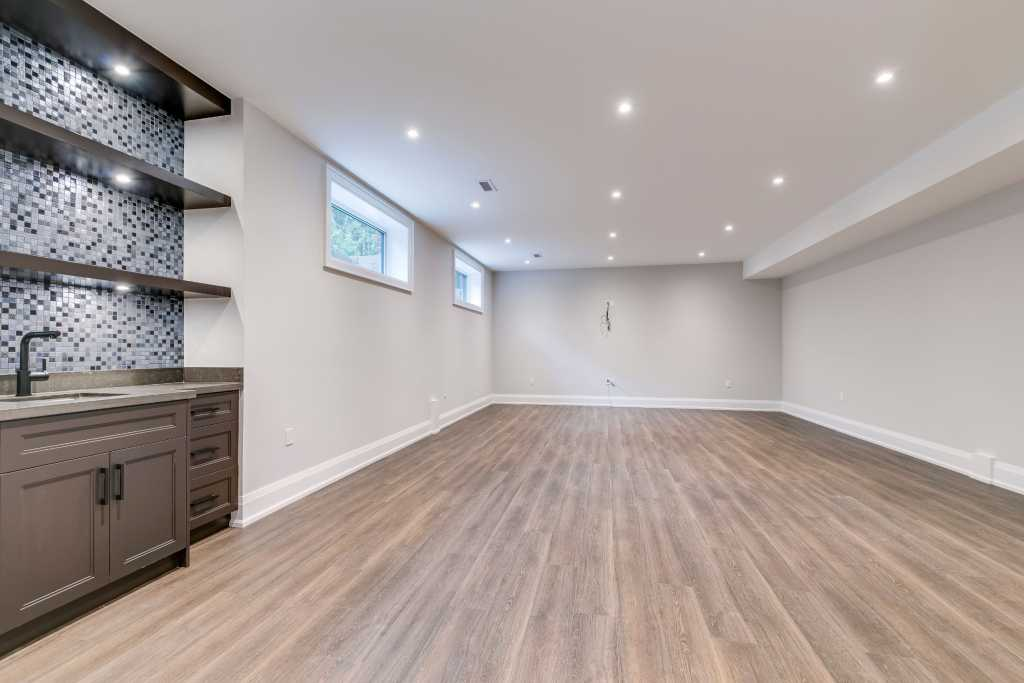 open space basement with wet bar - basement design ideas by black pearl custom homes