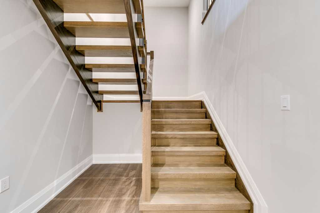 basement staircase with wooden stairs and railings