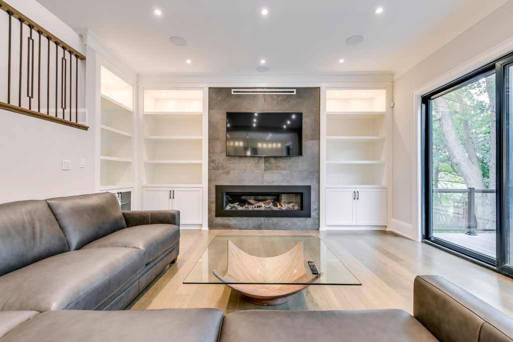 luxury living room with build in entertainment unit and marble tile wall decor - custom home renovations