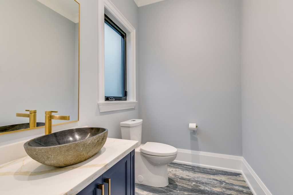 custom bathroom with blue vanity and golden frame wall mirror