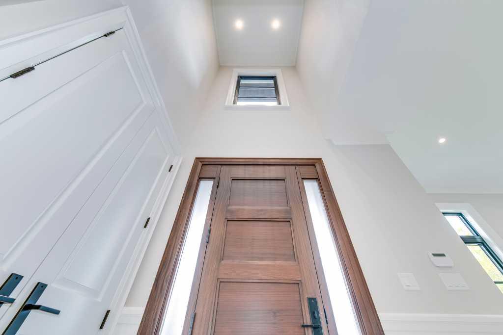 custom front door with small window above - new home builders in toronto
