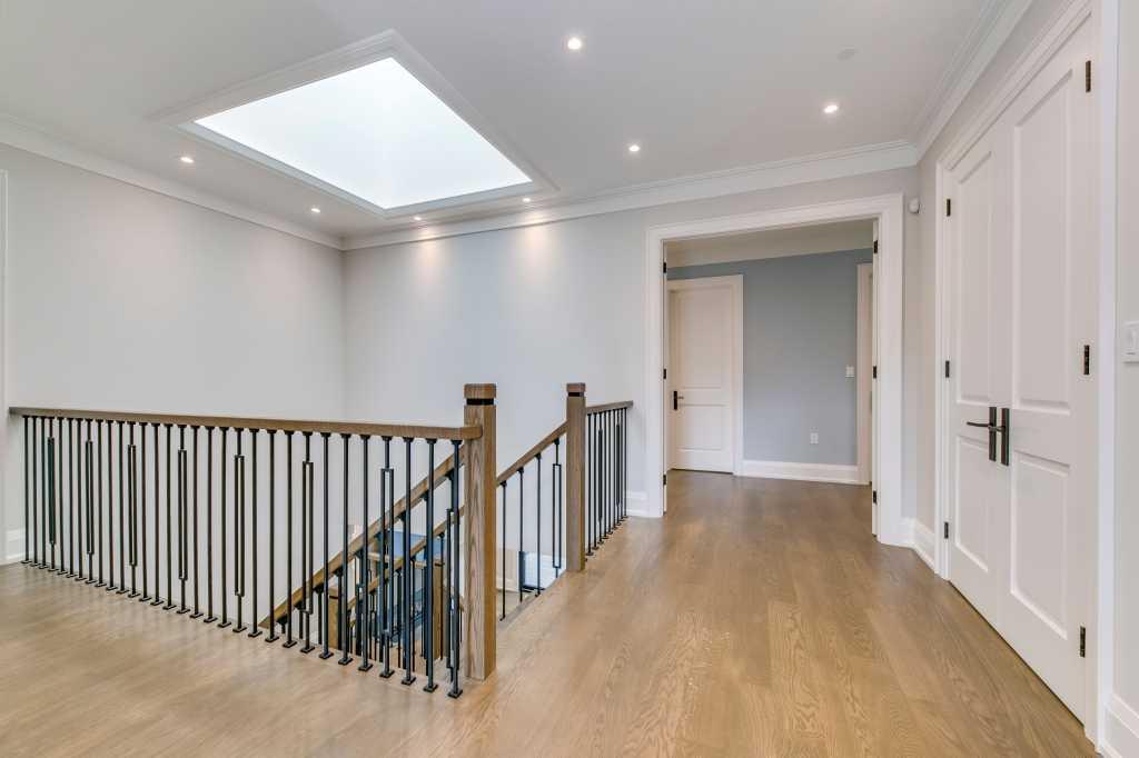 second floor hallway with custom railings and wooden floor - toronto home builders