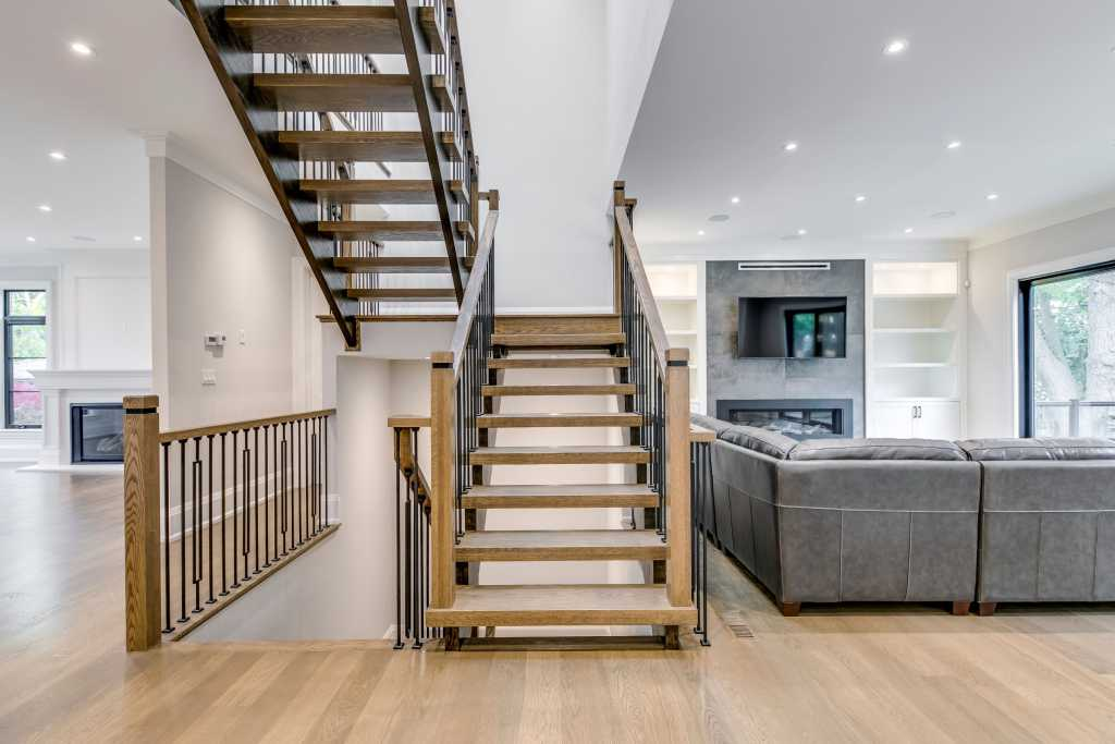 custom staircase and living room in amazing home by black pearl custom homes