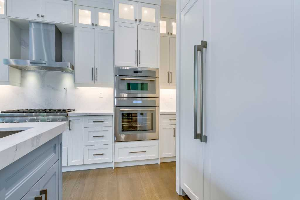 custom kitchen with white kitchen cabinets and blue islande