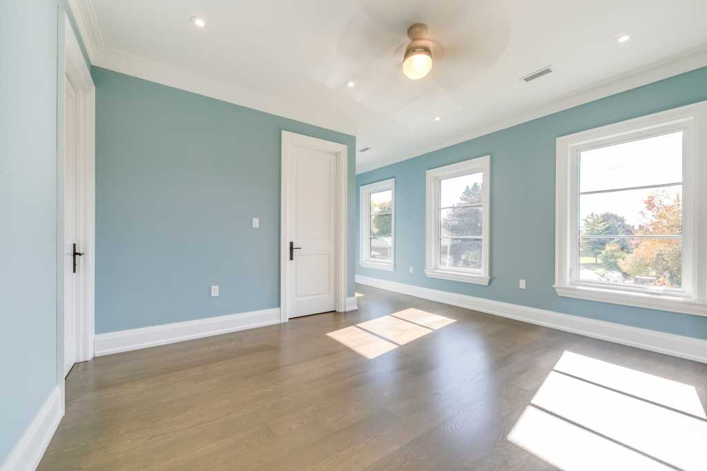custom second floor bedroom with crown moulding and baseboard trim