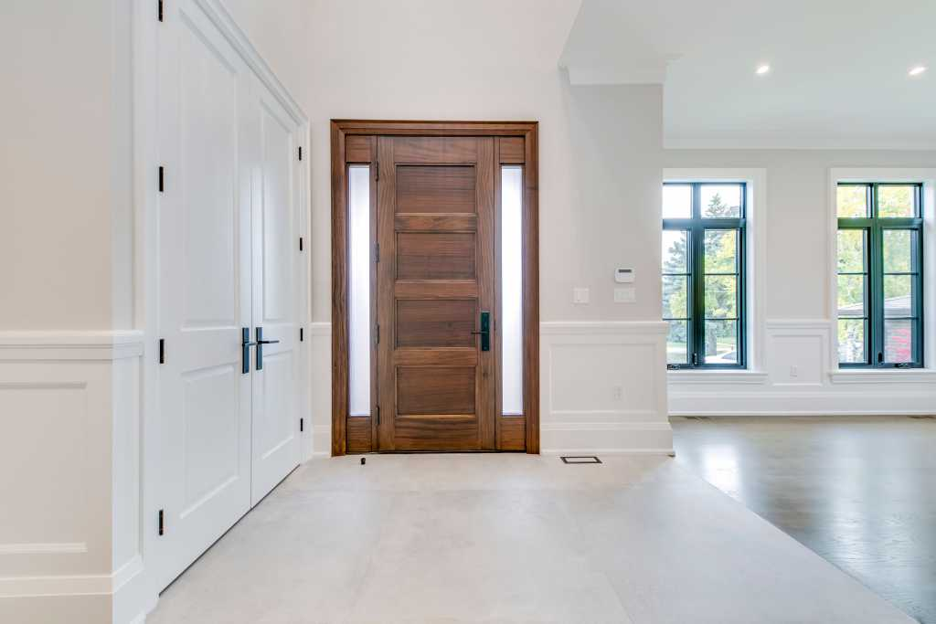 front door in amazing hallway with Wainscoting wall trim - custom home renovations