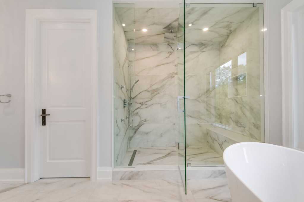 custom shower with marble splash tiles and glass enclose